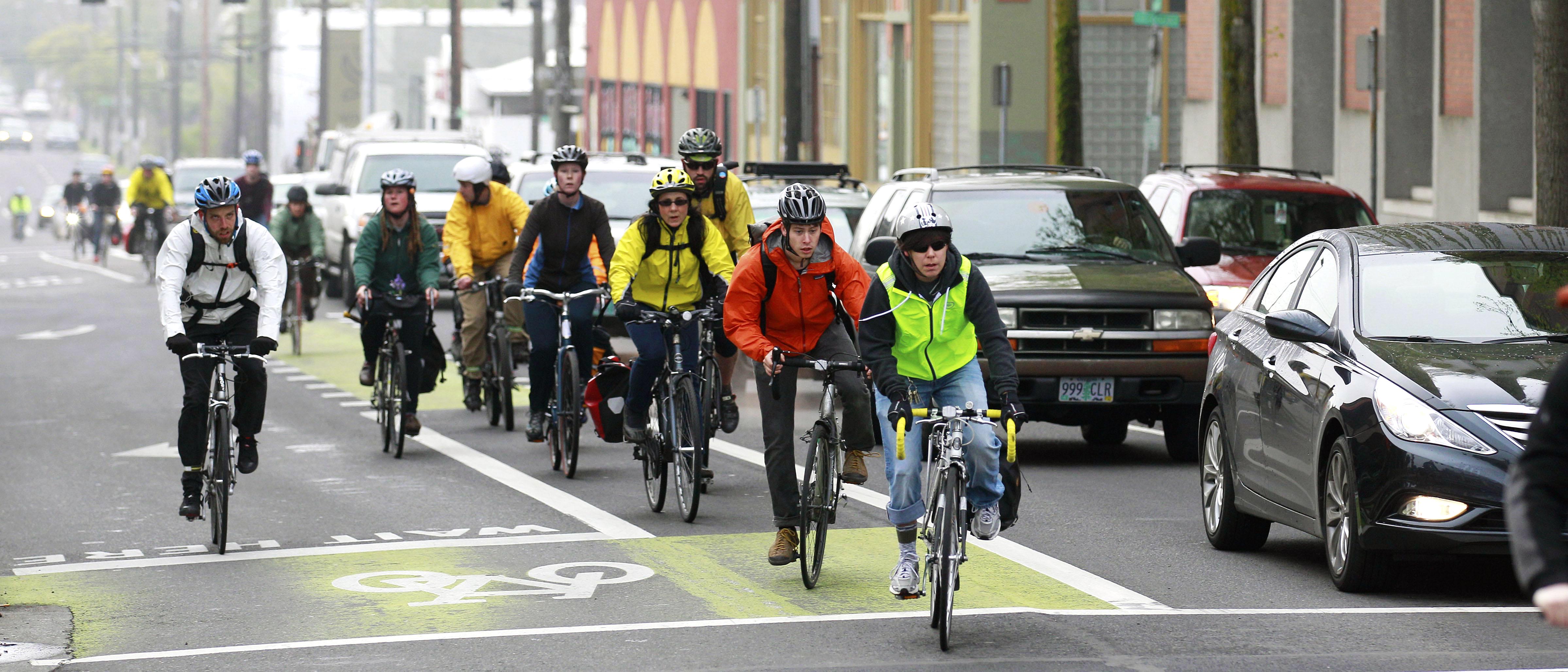 Group of people biking through city (© AP Images)