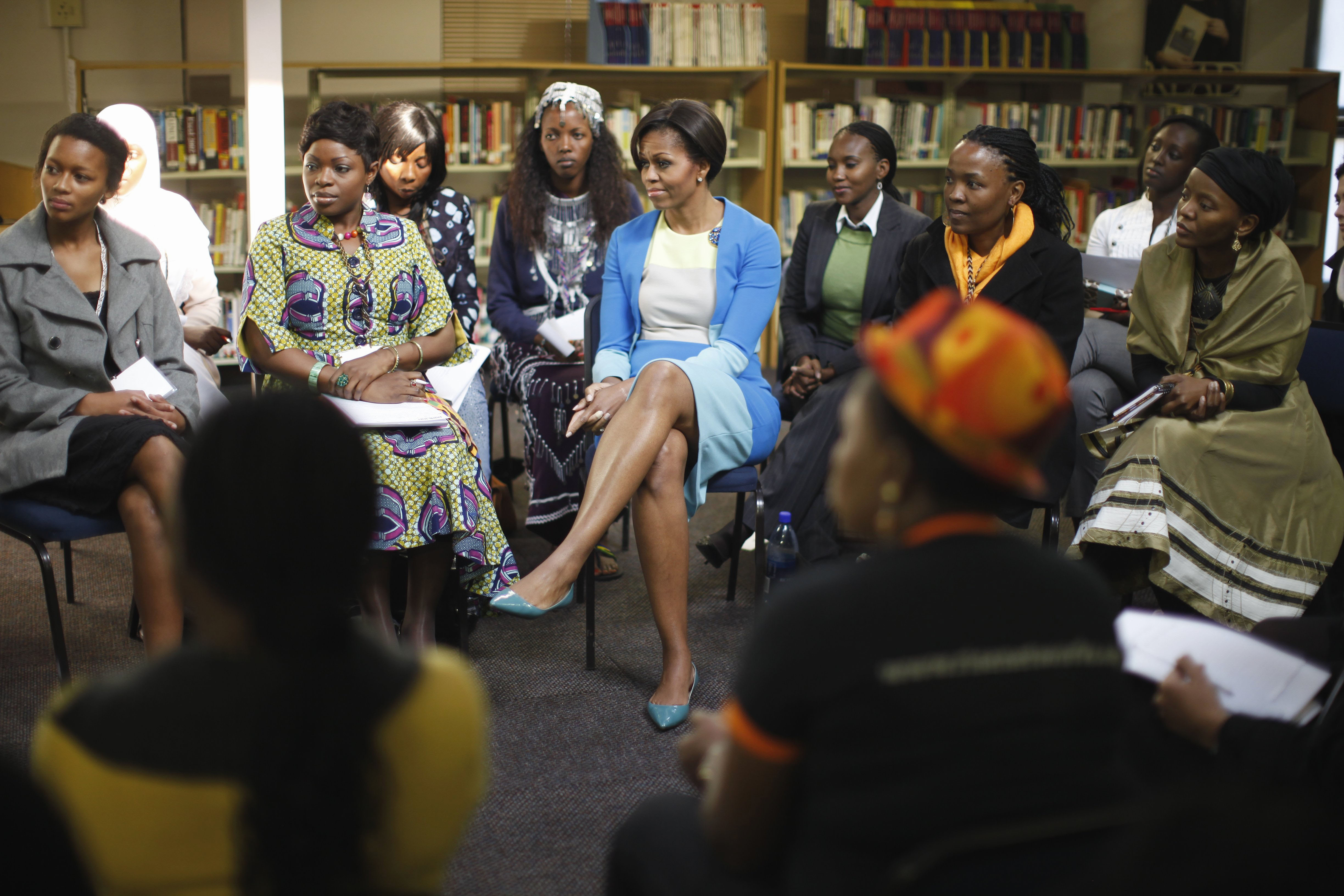 Michelle Obama seated with small group of young African women (© AP Images)