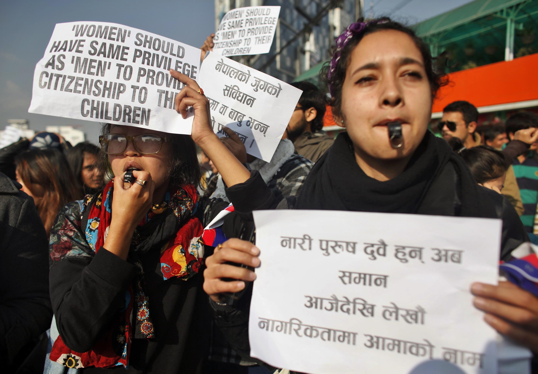 گروهی از زنان نشان هایی در دست دارند. (عکس از آسوشیتدپرس)