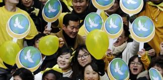 Une foule de gens tenant des ballons et des pancartes (© AP Images)