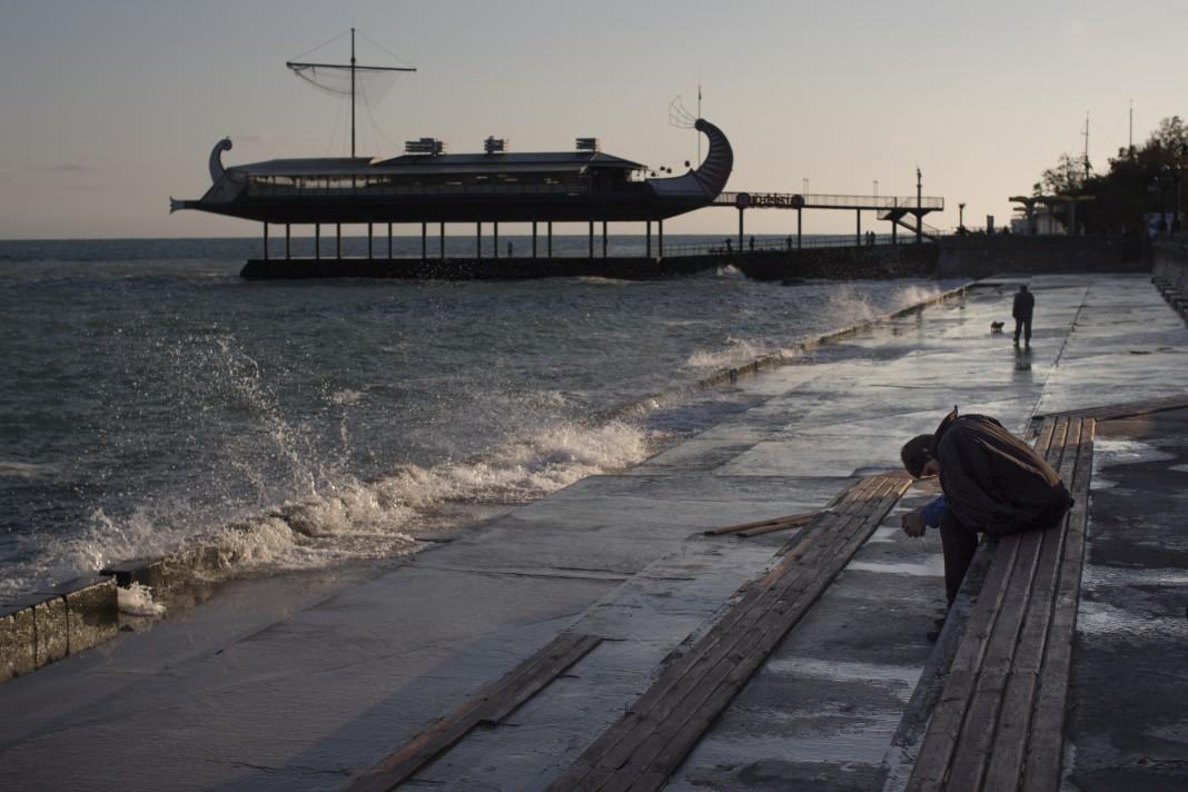 Un jeune homme assis sur un banc, tête baissée, sur un remblai devant la mer, avec un bâtiment sur pilotis en arrière-plan (©AP Images)