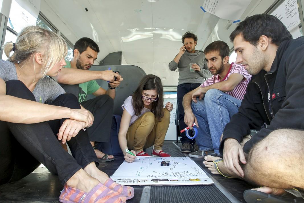 Des jeunes accroupis regardent un schéma par terre (© AP Images)