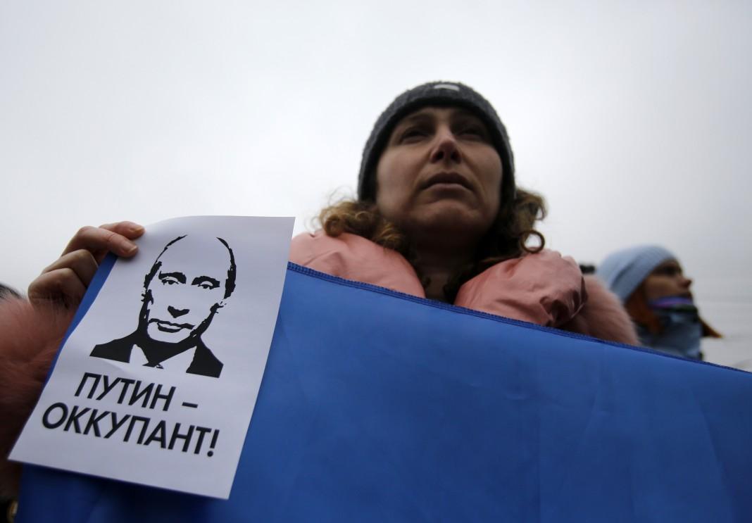 Une manifestante tenant une banderole (© AP Images)