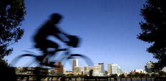 Person riding bike with city skyline in background (© AP Images)