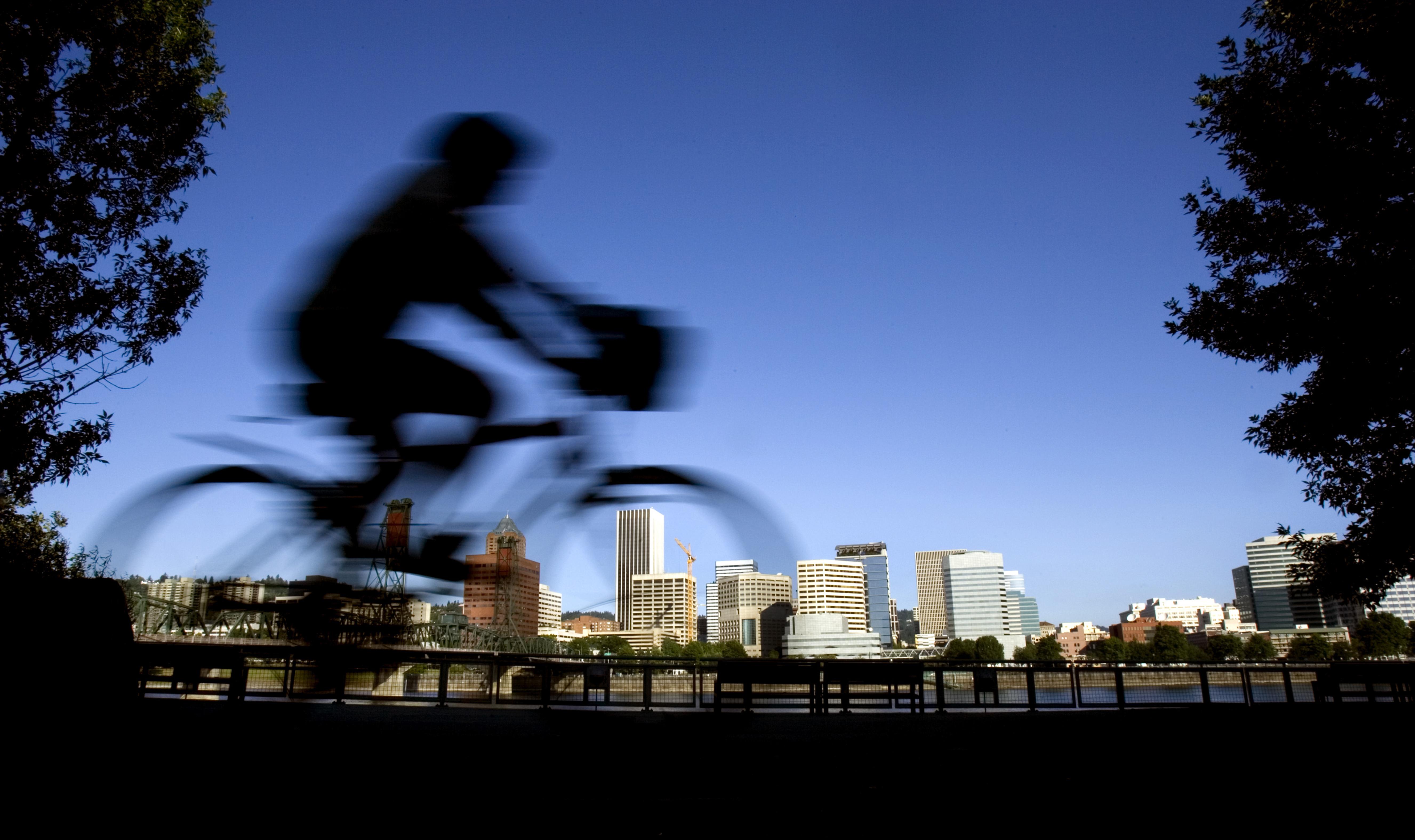 Cycliste passant devant des bâtiments. (© AP Images)