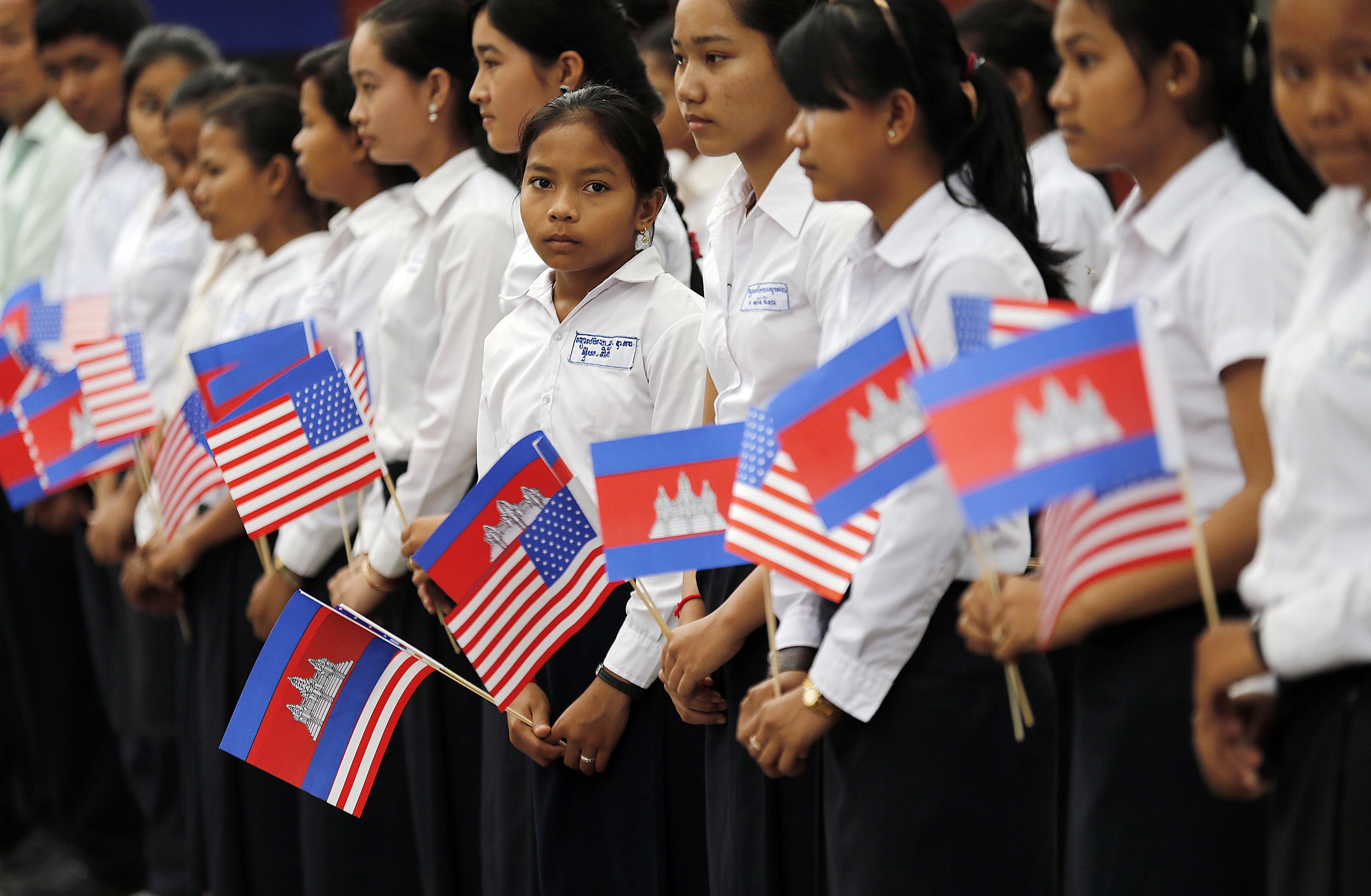 Un groupe d'adolescentes, alignées, tenant des drapeaux cambodgiens et américains (© AP Images)