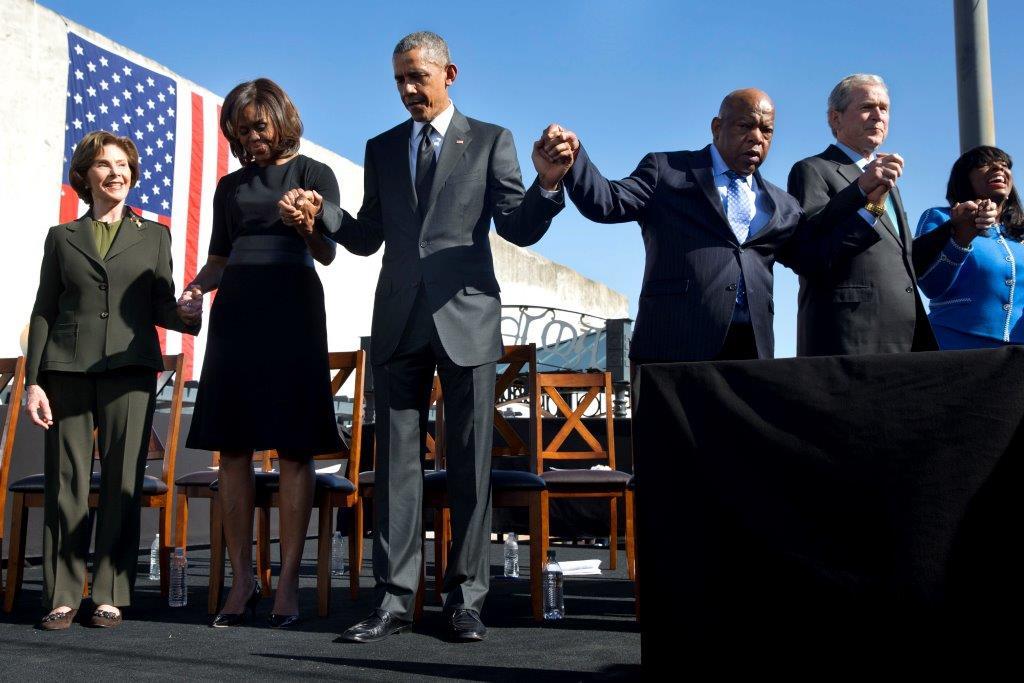 لورا بوش، میشل اوباما، پرزیدنت اوباما، جان لوئیس، جورج دبلیو بوش، و تری سئول، نماینده کنگره، دست در دست یکدیگر نهاده اند. (عکس از آسوشیتد پرس)