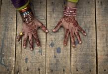 Deux mains décorées de signes peints au henné (© AP Images)