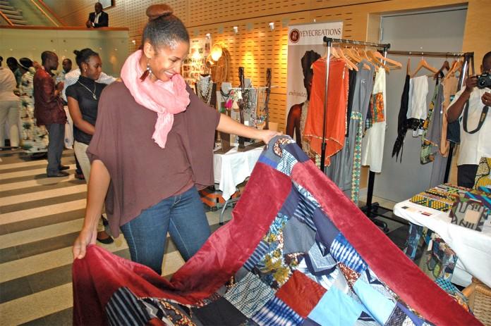 زنی که درغرفه نمایشگاه بازرگانی مشغول تماشای کالایی است (وزارت امور خارجه)