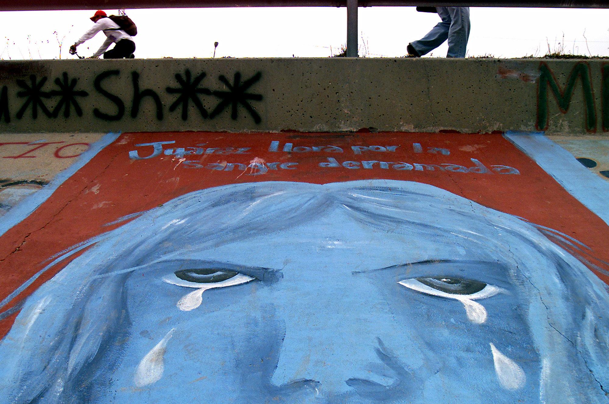 Fresque peinte sur un mur de béton, représentant le visage d'une femme en pleurs (© AP Images)