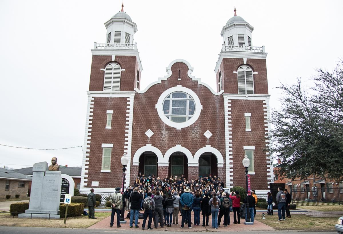 Grupo de personas en las escalinatas y el atrio de una iglesia (© Perple Mudd)