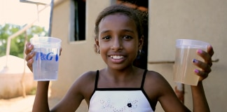 Girl holding two cups of water, one clean, one dirty (P&G)