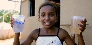 یک دختر یک لیوان آب کثیف و یک لیوان آب پاکیزه در دست دارد (P&G)