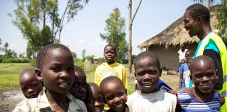 Group of smiling children with thatched hut and trees in background (USAID)