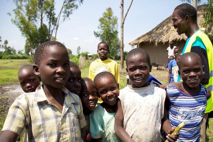 Grupo de niños sonrientes con árboles al fondo (USAID)