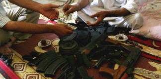 Guns and money changing hands in Iraq (© AP Images)