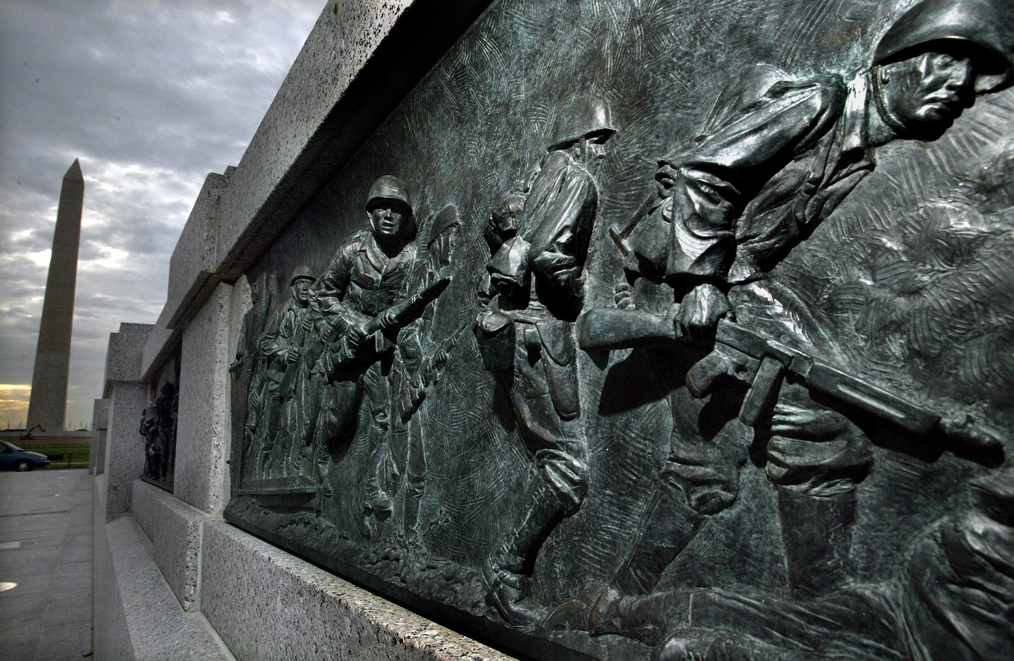 Bas-relief panel showing men in helmets holding weapons (© Ron Edmonds/AP Images)