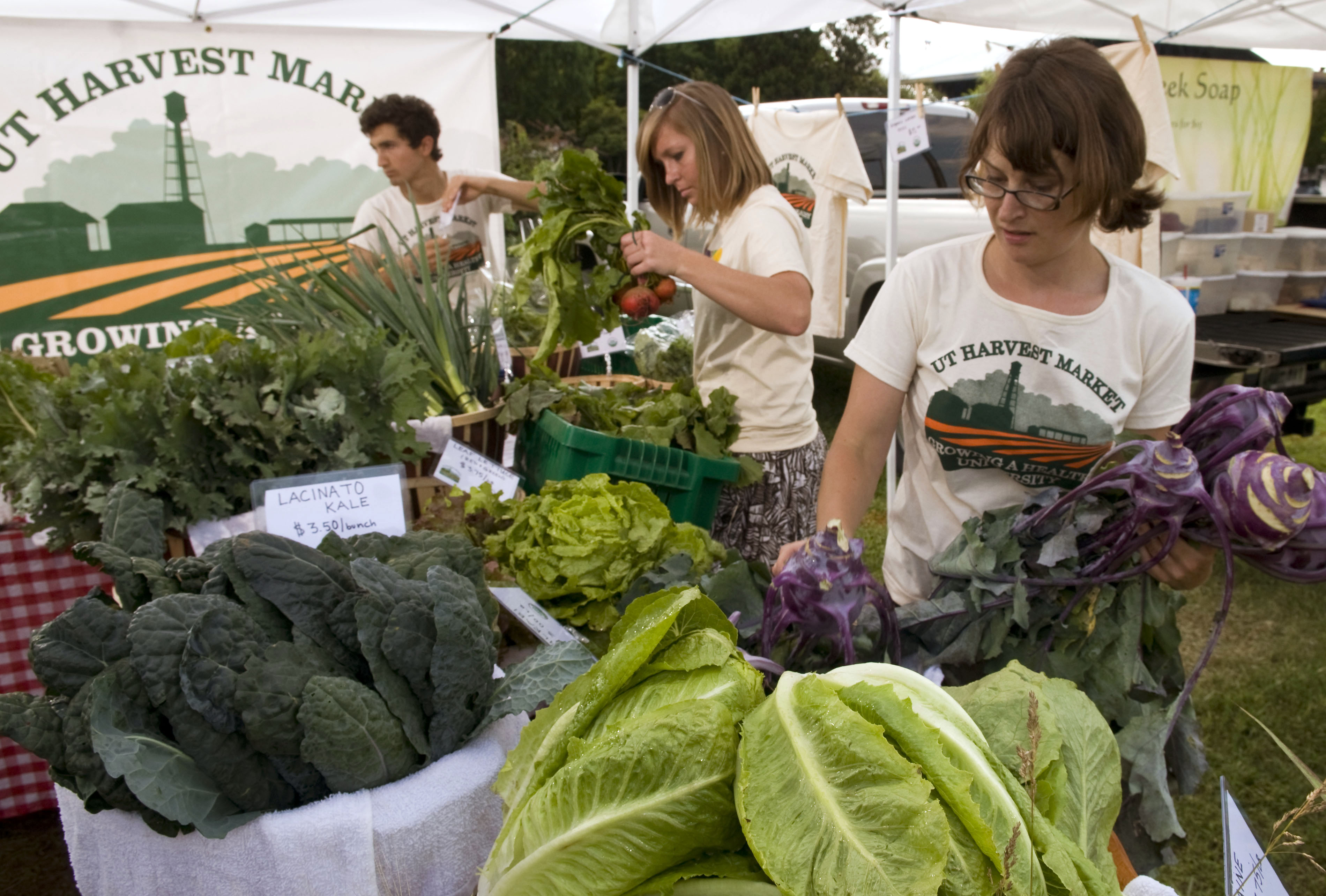 Trois personnes dans un stand à légumes, avec des légumes dans les mains (© AP Images)