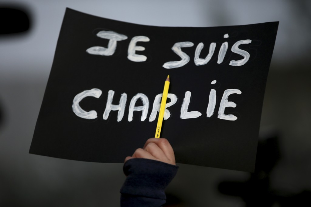 "Hand holding up ""Je suis Charlie"" sign and pencil (© AP Images)"