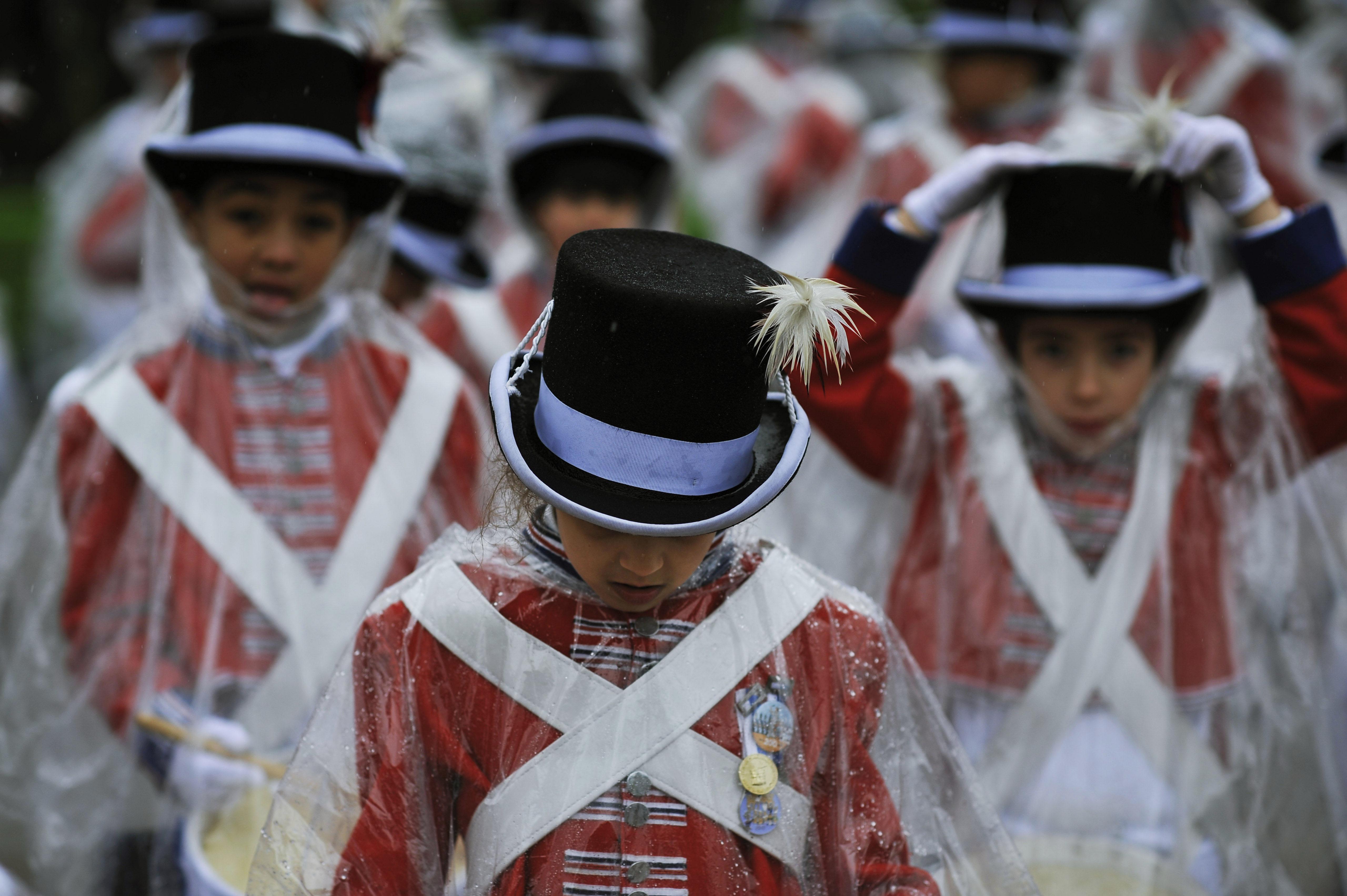 Des jeunes en costume festif, et portant un poncho contre la pluie, en train de défiler (© AP Images)