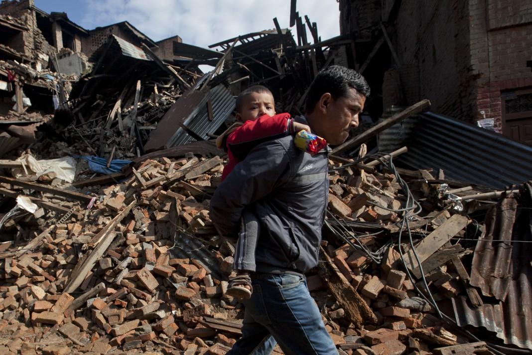 Hombre cargando a un niño delante de edificios destruidos por el terremoto (© AP Images)