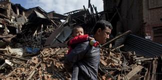 مردی در حال حمل یک کودک در جلو ساختمان هایی که در اثر زلزله ویران شده اند. (عکس از آسوشیتدپرس)