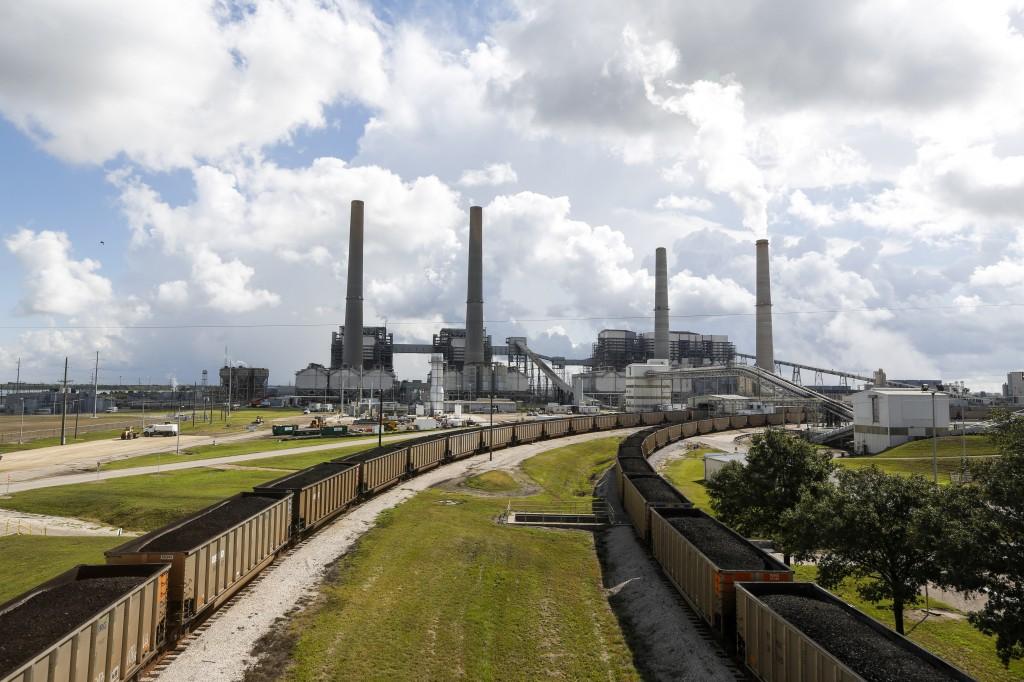 Vue d'une usine avec ses cheminées, en arrière-plan, et des wagons de charbon, au premier plan. (© AP Images)