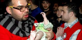 Un humanitaire syrien tenant un petit enfant dans les bras (© AP Images)