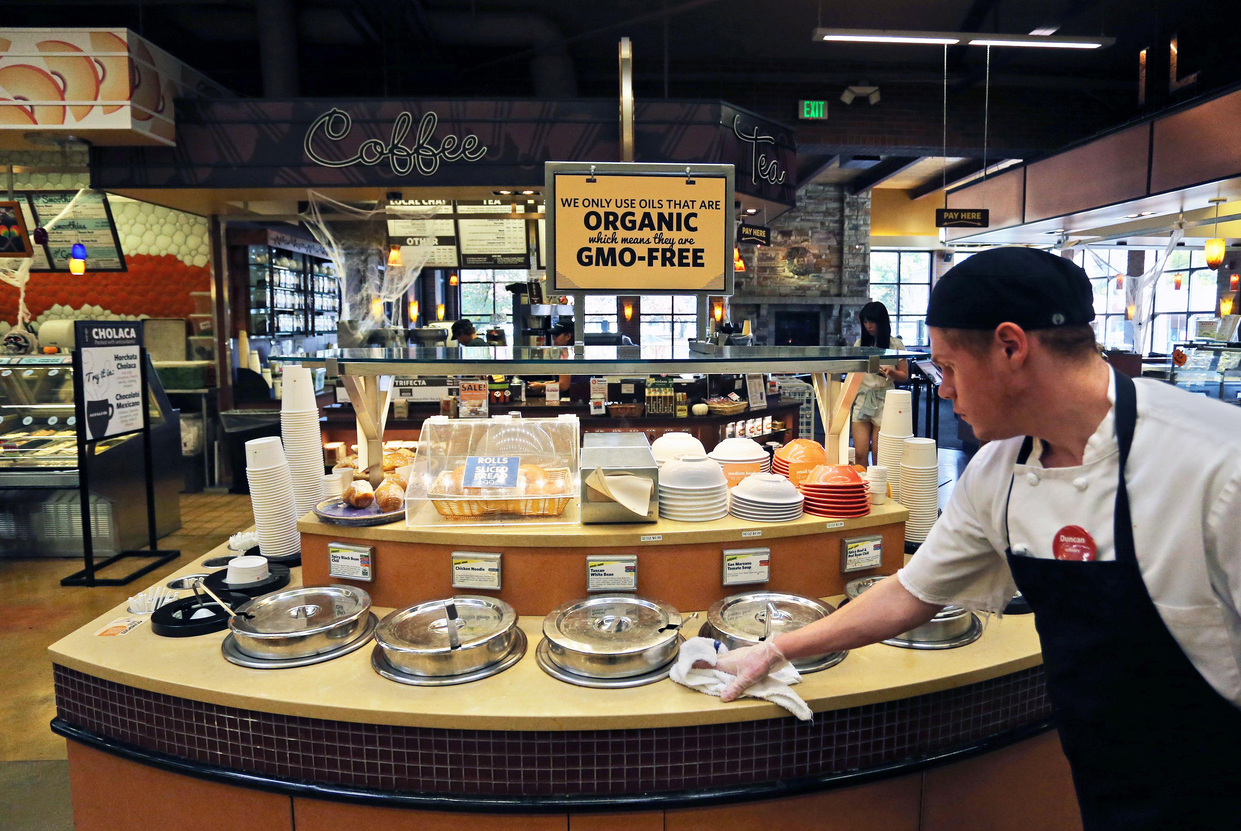 Plan d'un étalage de soupes fraîches, bio, vendues dans un supermarché, avec sur la droite, un homme habillé d'un tablier, qui essuie le comptoir avec un torchon (© AP Images)