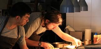 Deux cuisiniers affairés à préparer des assiettes posées sur un comptoir (Creative Commons)