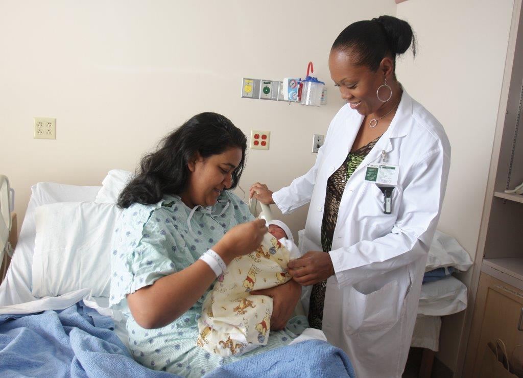 Dr Achong observant une maman et son enfant nouveau-né dans un lit d'hôpital (Seth Harrison)