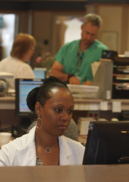 Le Dr Achong assise au travail, devant un ordinateur (Seth Harrison)
