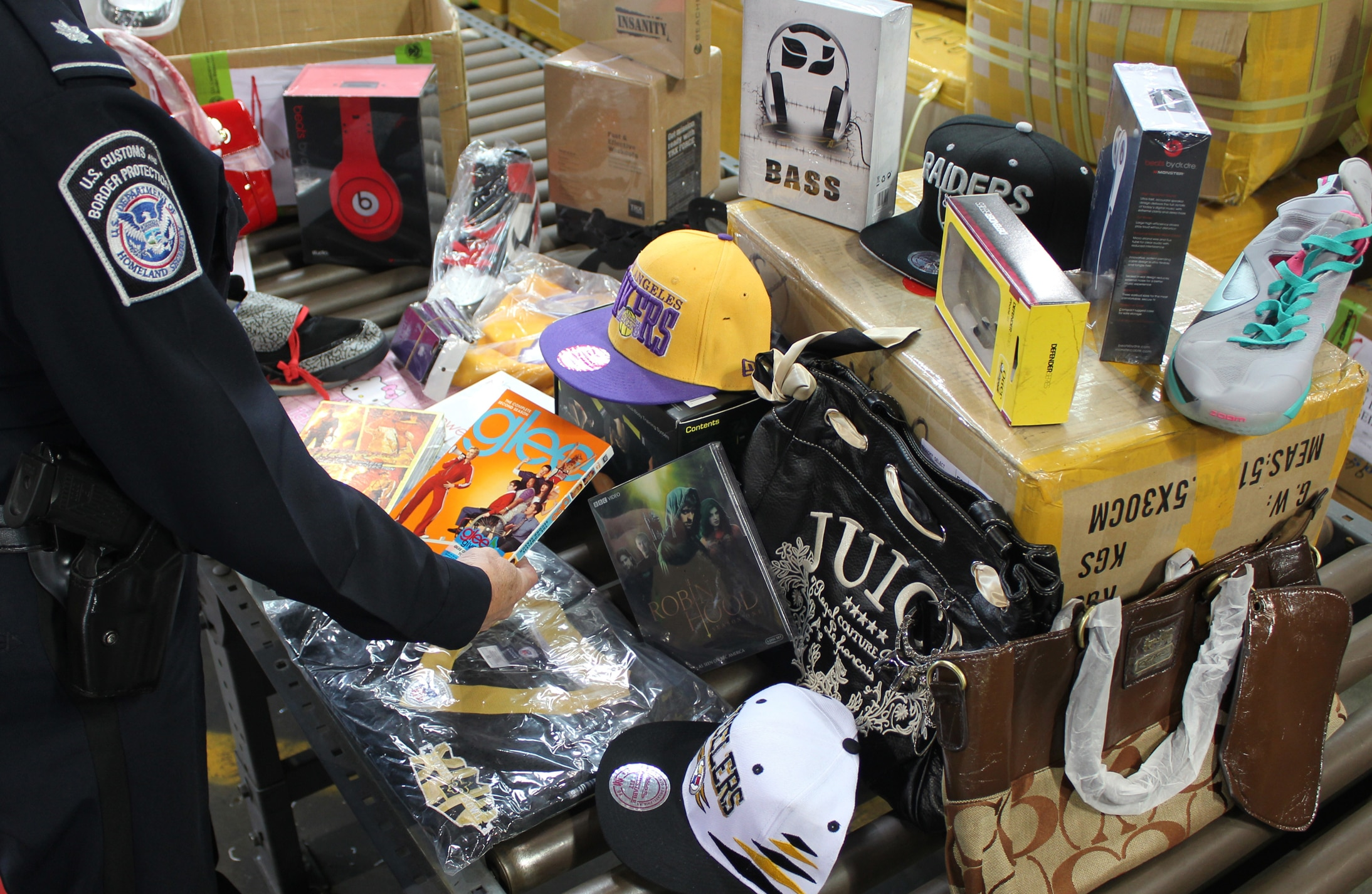 Federal agent examining seized counterfeit goods (U.S. Dept. of Homeland Security)