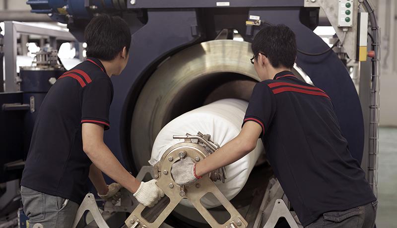 Deux travailleurs chargeant un rouleau de tissu dans une machine (Crédit photo : Nike)