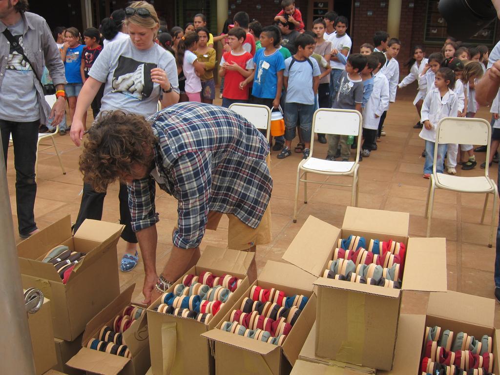 Personas abriendo cajas de zapatos, con un grupo de niños al fondo. (Foto cedida por TOMS Shoes/Flickr)
