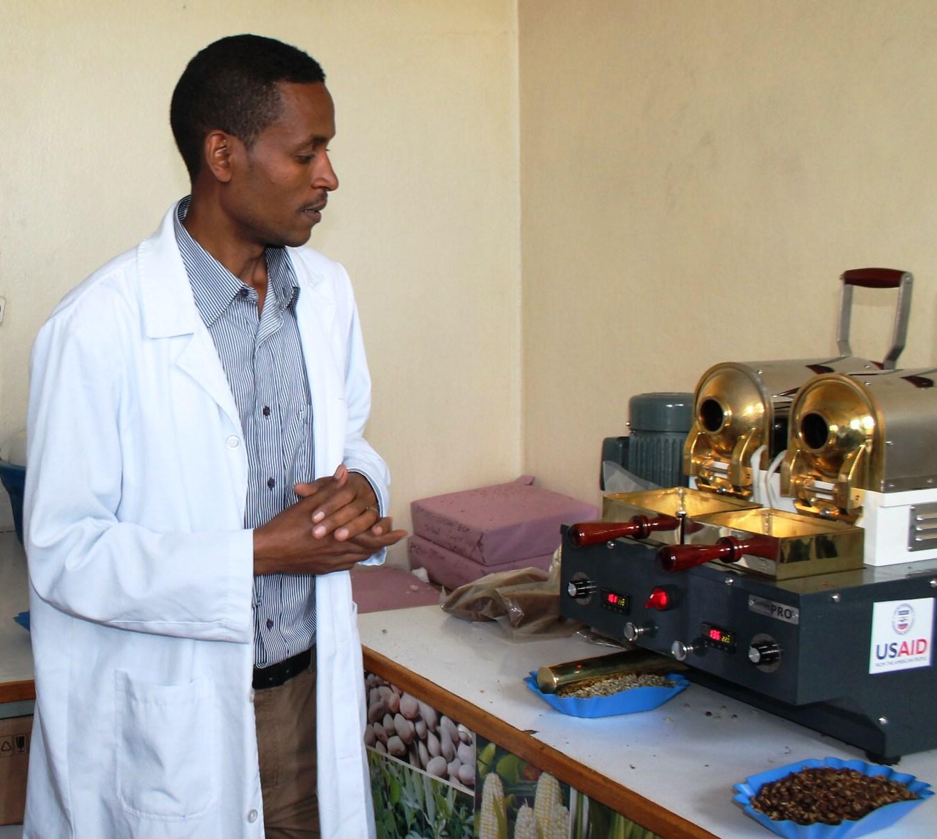 Homme en blouse blanche, debout devant deux machines à café (USAID)