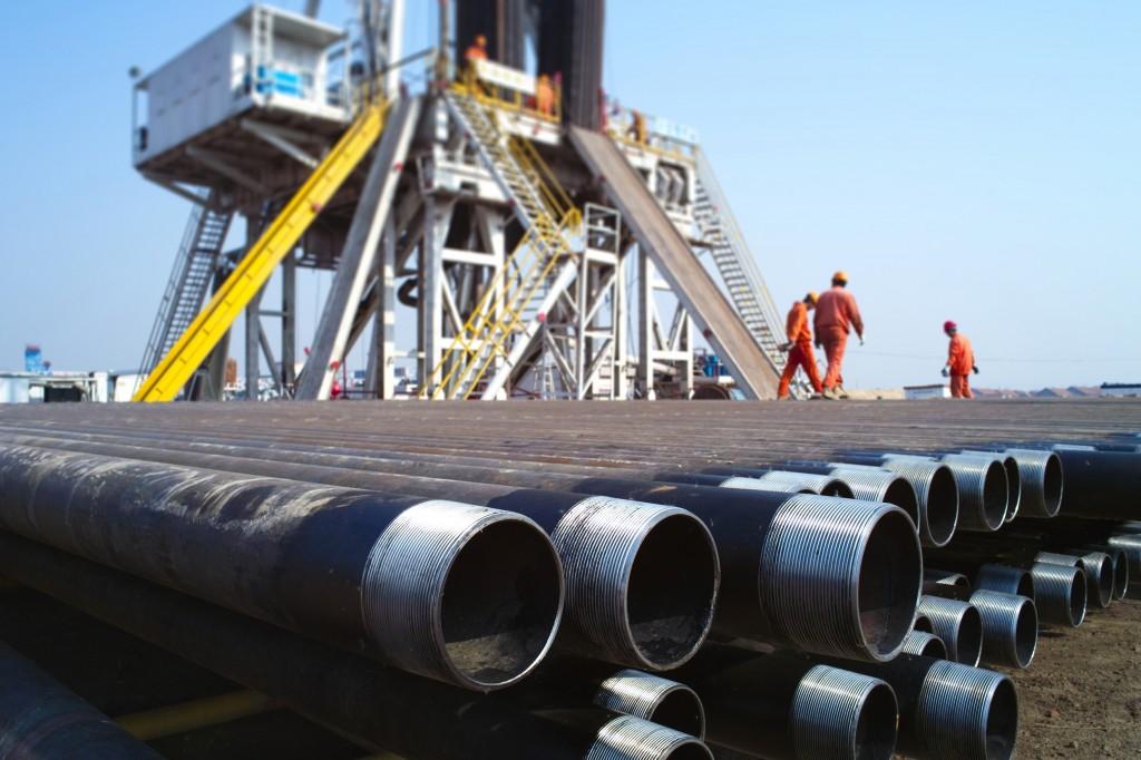 Pila de tubos de perforación, con plataforma de perforación al fondo. (zhuda/Shutterstock)