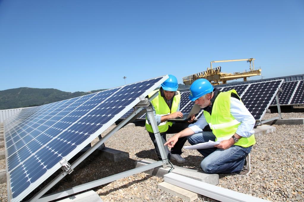Dos técnicos con cascos de protección examinan la instalación de paneles solares (Goodluz/Shutterstock)