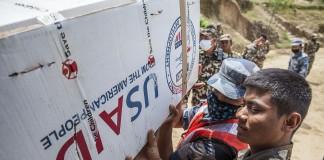 دو مرد در حالی که یک جعبه کمک های انسان دوستانه را حمل می کنند (USAID)