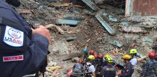 گروهی از نجات دهندگان که کلاه خود به سر دارند در میان ویرانه ها (USAID)