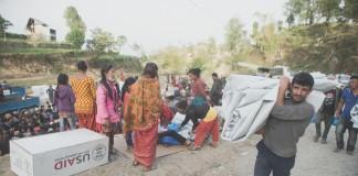 Hombre cargando una lona mientras otros esperan abastecimientos (USAID)