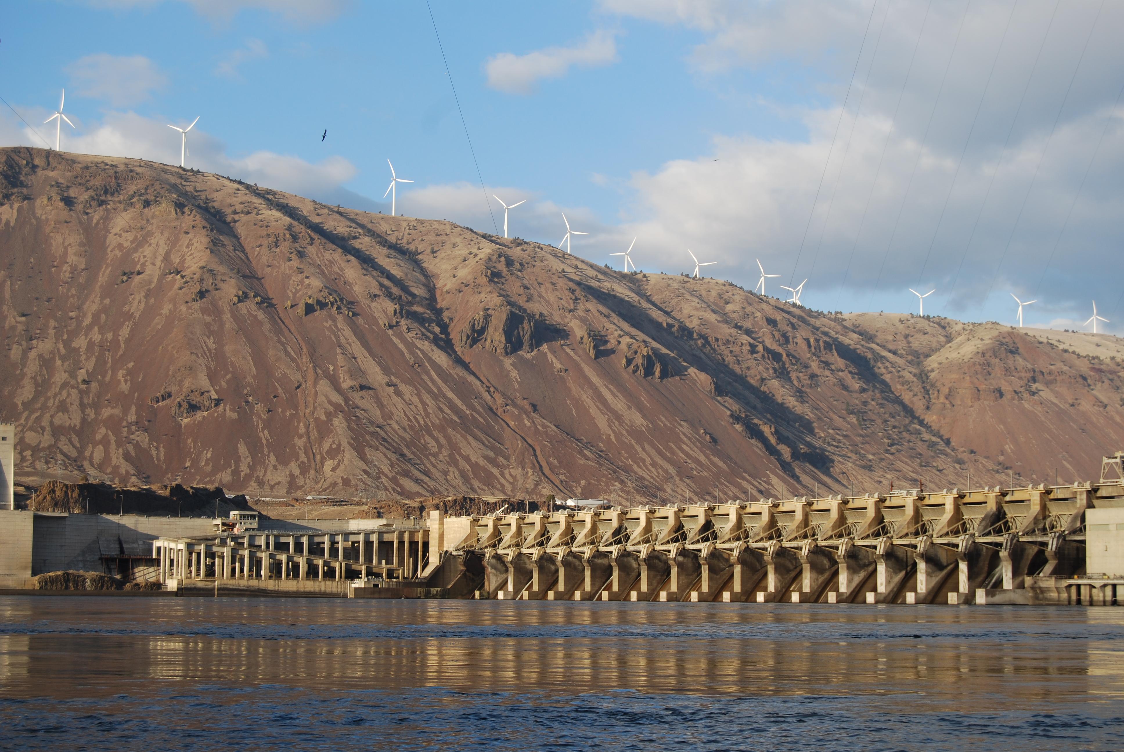 Des éoliennes le long d'une crête rocheuse, un barrage sur la rivière dans la vallée (MWH Global)