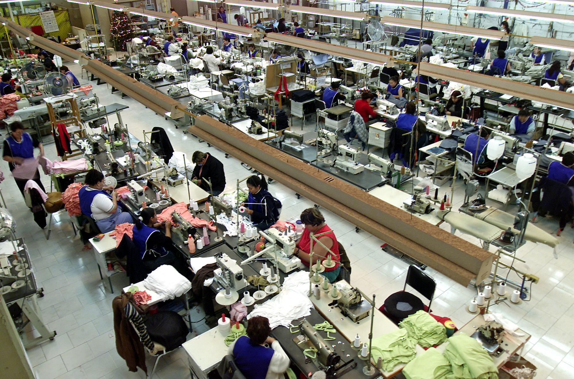 Des couturières assises en rangées en train de confectionner des vêtements destinés aux États-Unis (© AP Images)