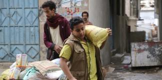 Dans une rue, un homme poussant une brouette chargée de dons alimentaires et, au premier plan, un garçon portant un sac de vivres sur l'épaule (© AP Images)