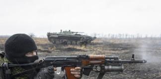 Un homme cagoulé tire avec une arme à feu au premier plan ; à l'arrière-plan, un char (© AP Images)