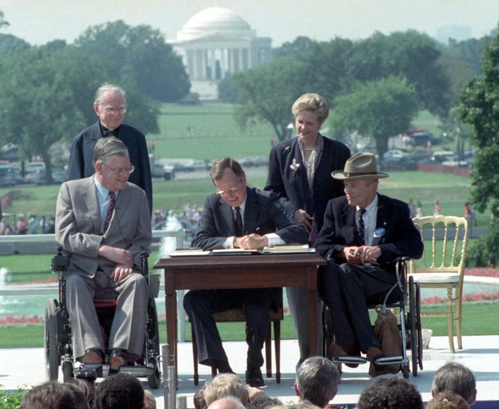 Le président George H. W. Bush signant un document sur une table extérieure, deux hommes en fauteuil roulant à côté de lui (© AP Images)