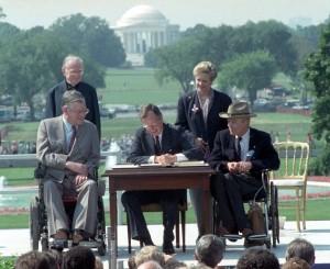 George H.W. Bush en train de signer un document à une table en plein air sous le regard d'autres personnes (© AP Images)