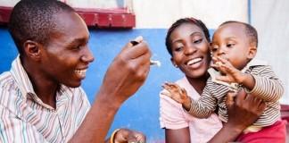 Hombre con una cuchara con comida junto a una mujer con un niño (Feed the Future)