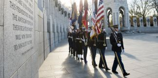 Military honor guard marching in formation at WWII memorial (© Saul Loeb/AFP/Getty Images)
