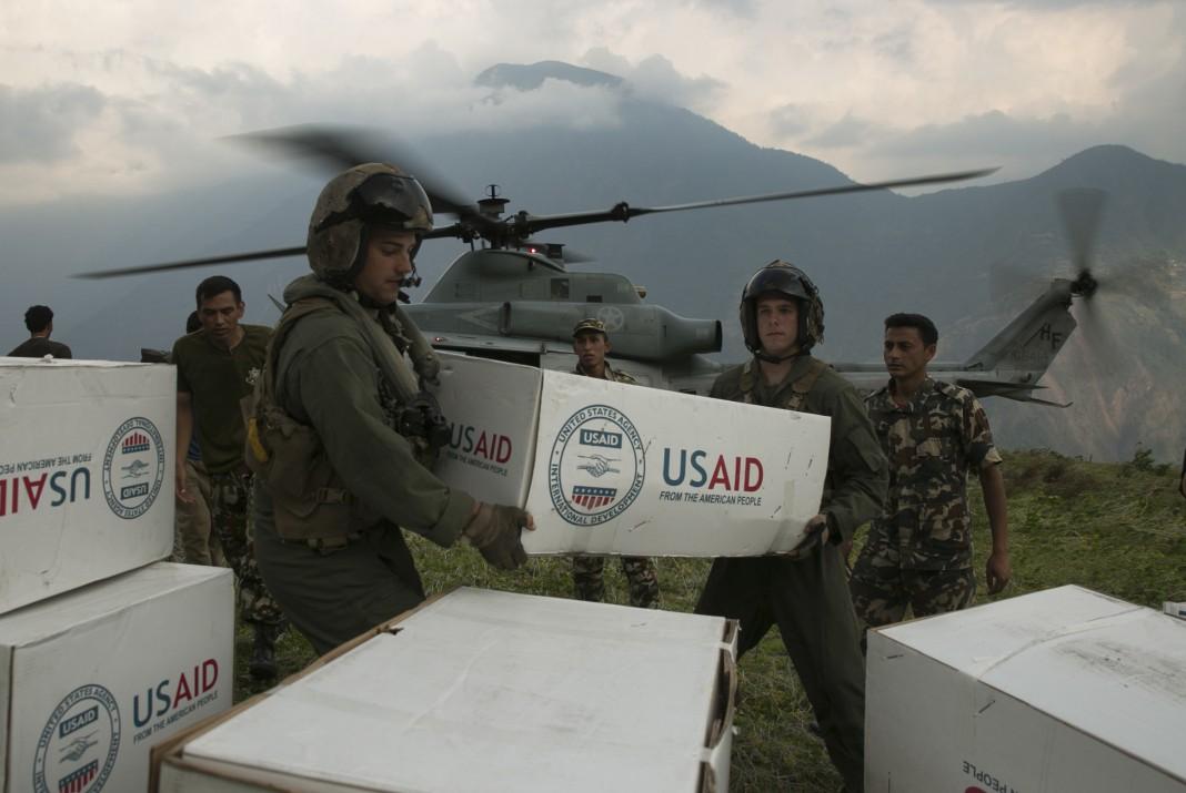Infantes de marina de Estados Unidos y soldados nepalíes llevan cajas de suministros marcadas con el rótulo 'USAID' de un helicóptero (DOD)